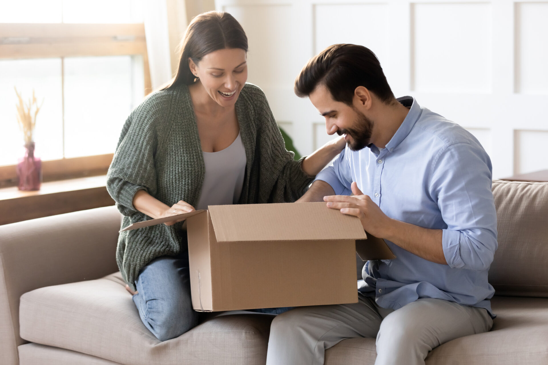 Overjoyed young married couple unpacking cardboard box at home.
